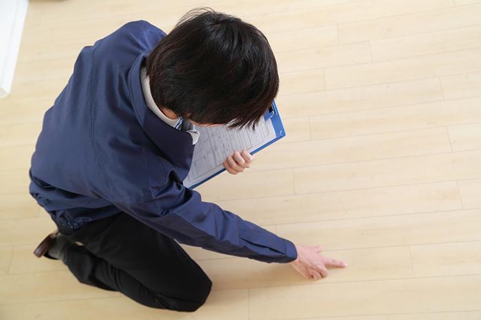 クリップボードを手に床の状態を確認している作業着の男性