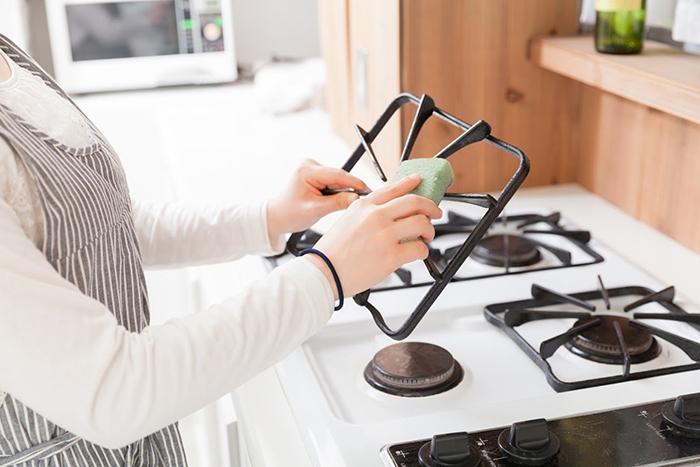 ガスコンロを拭き掃除している女性の手